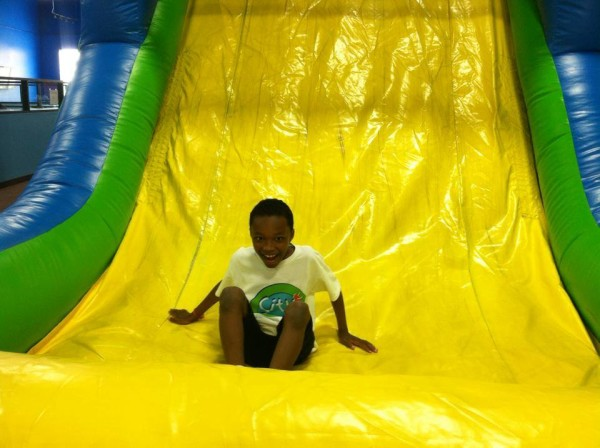 BOY ON GIANT SLIDE COLORFUL